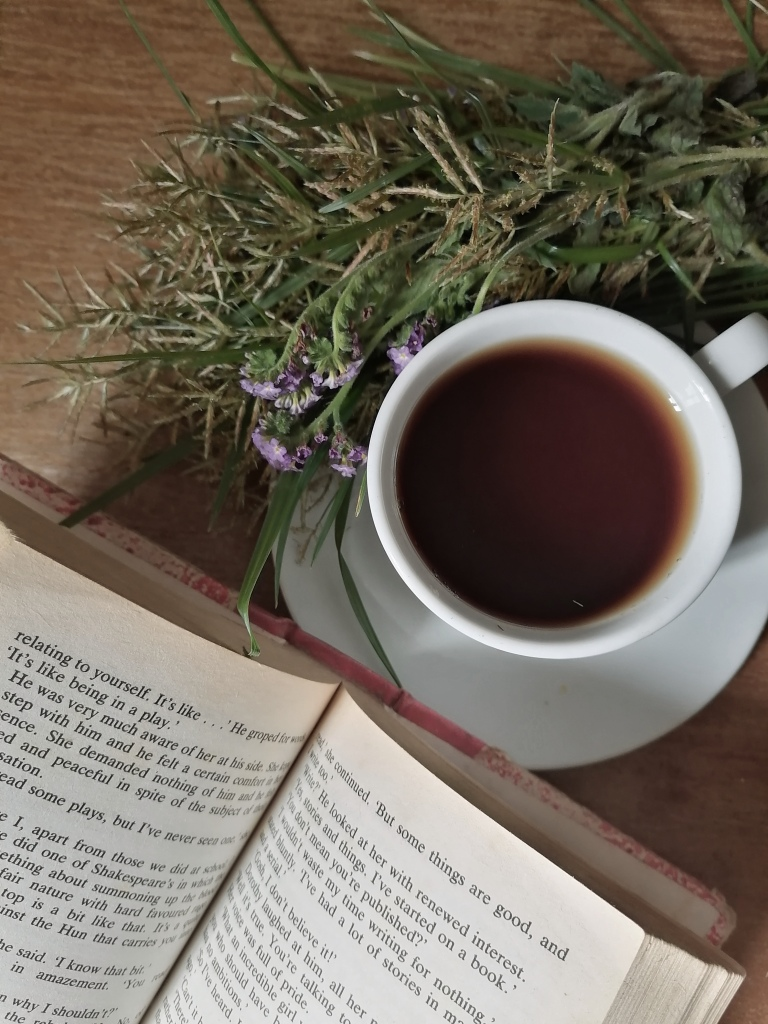 Opened book, coffee and flowers