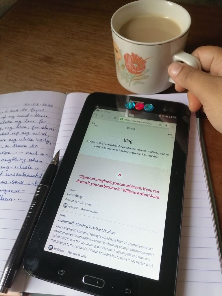 hand holding mug of tea with milk, alongside diary, tablet showing blog site, and fountain pen