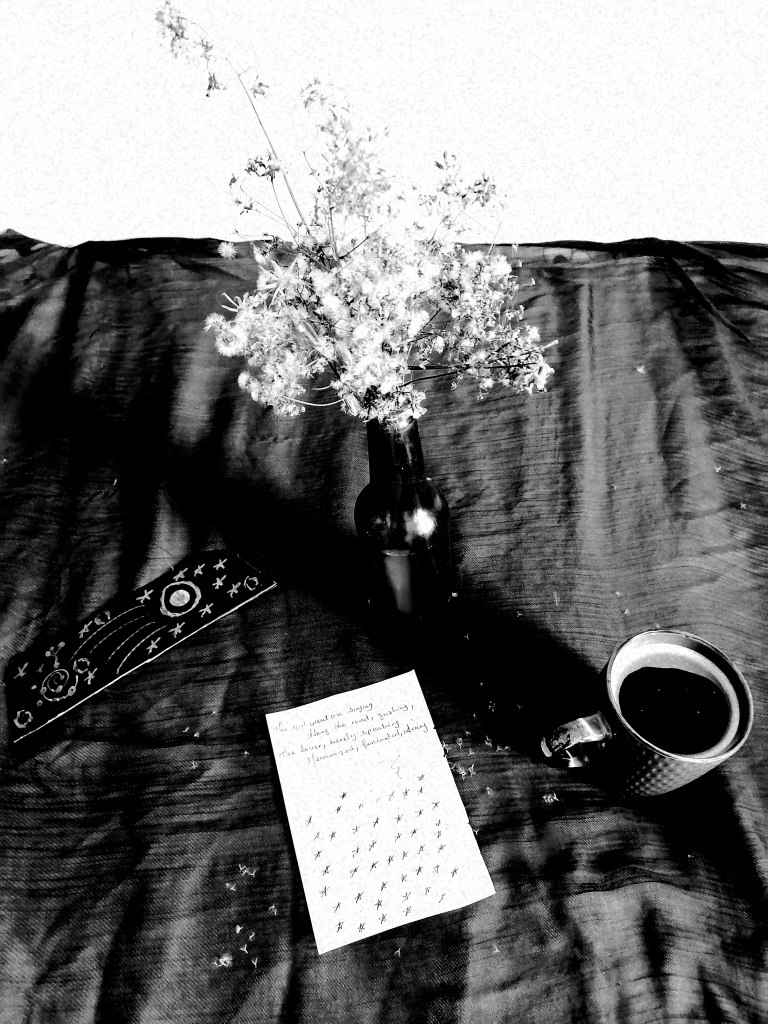 Black white photo of flowers in a bottle, a mug of black coffee, cosmic doodles, and a handwritten note